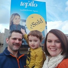 Photo of family standing in front of Sold poster