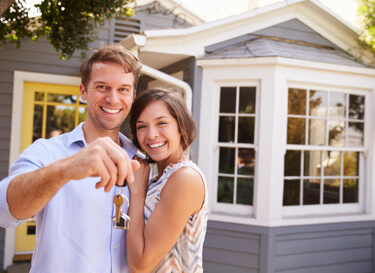 Photo of two people with a set of keys in front of a house