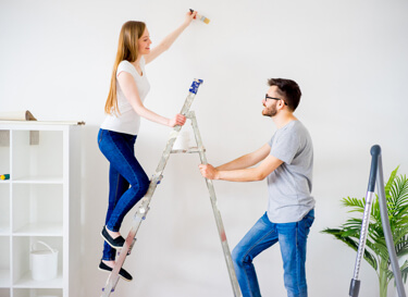 Photo of two people repainting a room